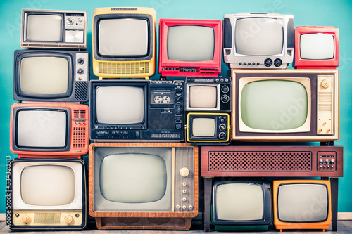 Obraz Retro TV receivers set from circa 60s, 70s and 80s of XX century, old wooden television stand with amplifier front mint blue wall background. Broadcasting, news concept. Vintage style filtered photo - fototapety do salonu