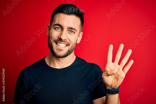 Fotomural Young handsome man wearing casual black t-shirt standing over isolated red background showing and pointing up with fingers number four while smiling confident and happy