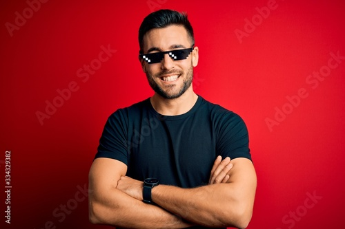 Fotografia Young handsome man wearing funny thug life sunglasses over isolated red background happy face smiling with crossed arms looking at the camera