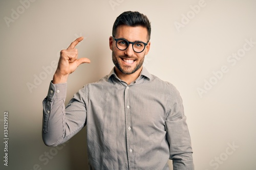 Young handsome man wearing elegant shirt and glasses over isolated white background smiling and confident gesturing with hand doing small size sign with fingers looking and the camera Wallpaper Mural