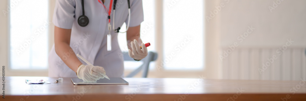 Fototapeta Close up view of female doctor writing blood tests on digital tablet in examination room