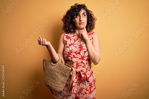 Vászonkép Young curly arab woman on vacation wearing floral dress and sunglasses holding w