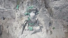 Overhead Vertical Drone Shot Over The Giant Buddha Statue With Bamboo Scaffolding In Construction , Carved Into The Rock Face Of The Hill