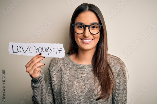 Photo Young beautiful brunette woman wearing glasses holding paper with love yourself