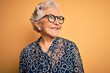 canvas print picture - Senior beautiful grey-haired woman wearing casual shirt and glasses over yellow background looking away to side with smile on face, natural expression. Laughing confident.