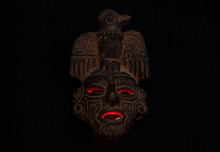 An Ancient Ceramic Pre Columbus Mask Based In American Indigenous Tribes Art Iluminated By Red Light Inside Over Black Background