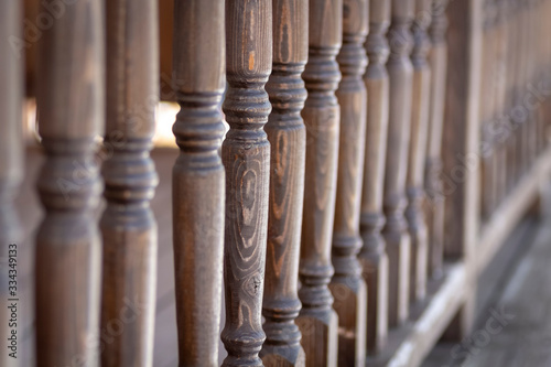 Photo A row of balusters of a wooden veranda.