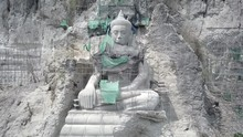Aerial Shot Flying Back Revealing  The Giant Buddha Statue With Bamboo Scaffolding In Construction , Carved Into The Rock Face Of The Hill