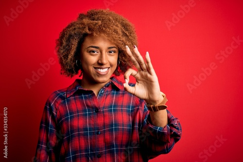 Young beautiful African American afro woman with curly hair wearing casual shirt smiling positive doing ok sign with hand and fingers Wallpaper Mural