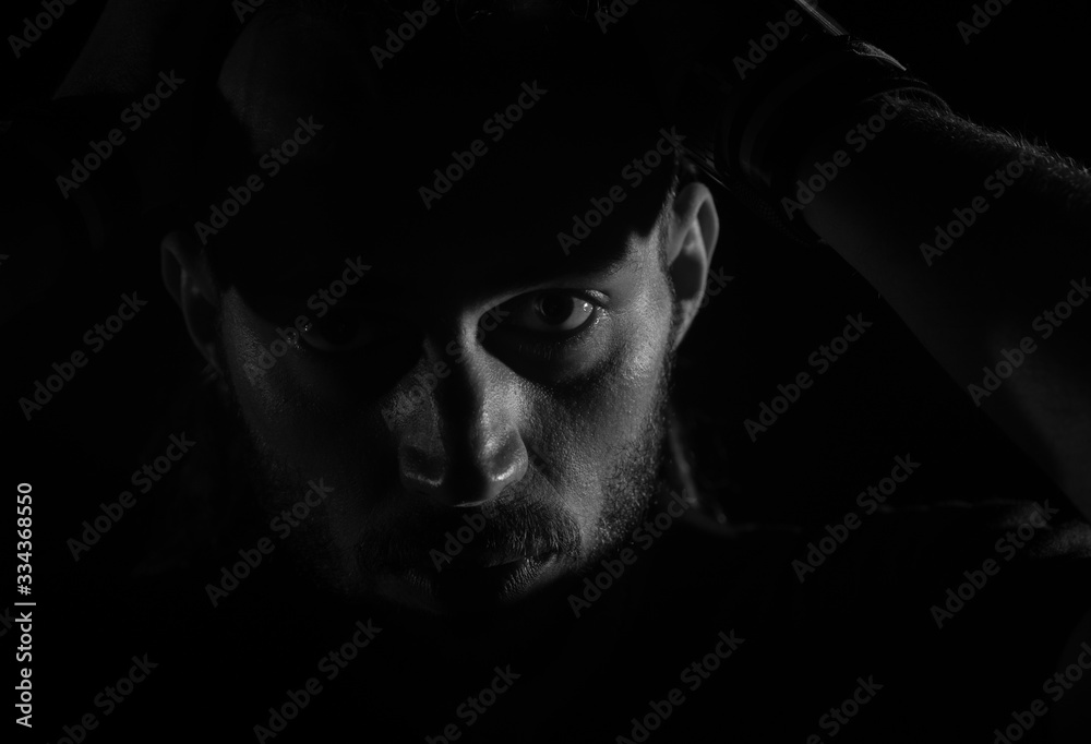 Fototapeta Dramatic portrait of male person looking at camera on dark background