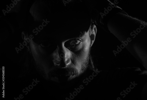 Dramatic portrait of male person looking at camera on dark background Canvas Print
