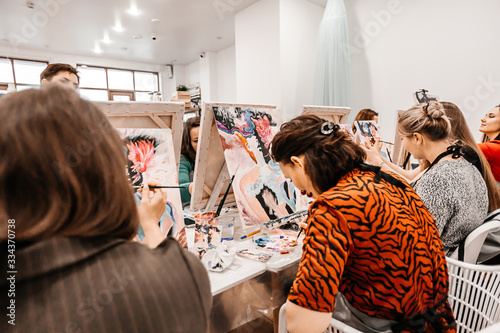 Young women paint with brushes on easels in art class Fototapete