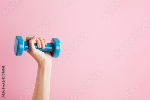 Womans hand holding blue dumbbell isolated on pink background Fototapete