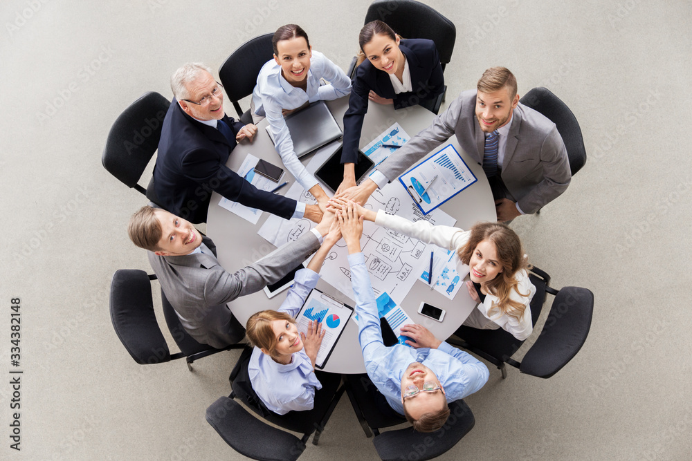 Fototapeta corporate, people and teamwork concept - happy business team sitting at table stacking hands