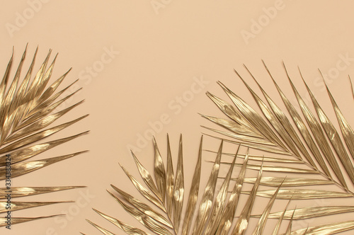 Gold colored tropical palm leaves on beige background flat lay top view copy space. Creative summer background with tropical leaves. Golden background, minimal nature concept