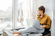Young woman dressed casually working on laptop while sitting on the window sill at home. Work from home at cozy atmosphere concept
