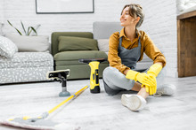 Portrait Of A Young And Cheerful Housewife Dressed For Work Sitting With Cleaning Tools On The Floor At Home. Concept Of Easy House Cleaning