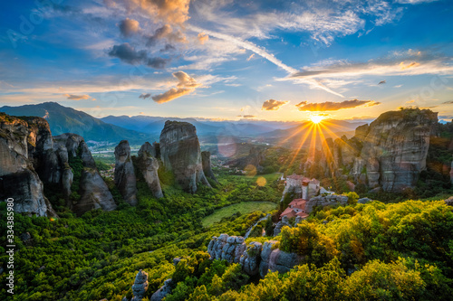Fototapeta Sunset over monastery of Rousanou and Monastery of St. Nicholas Anapavsa in famous greek tourist destination Meteora in Greece on sunset with sun rays and lens flare obraz
