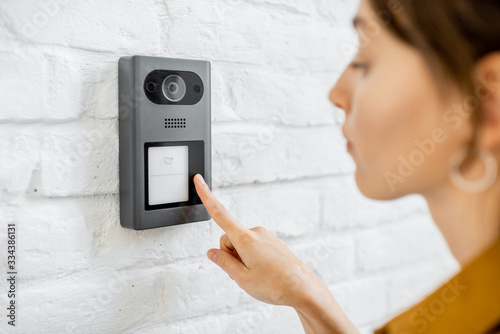 Woman rings the house intercom with a camera installed on the white brick wall Canvas-taulu