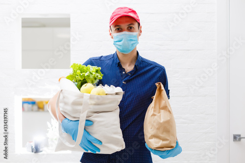 Fototapeta Courier's hands in latex white medical gloves deliver parcels in food packages to the door during the epidemic of coronovirus, COVID-19. Safe delivery of online orders during the epidemic. obraz