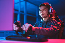 The Gamer With Headphones Sitting And Playing Video Games In The Neon Room