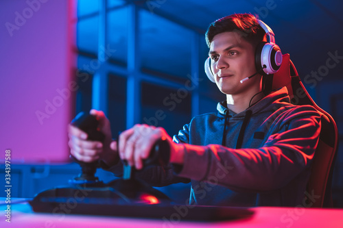 Papel de parede The gamer with headphones sitting and playing video games in the neon room