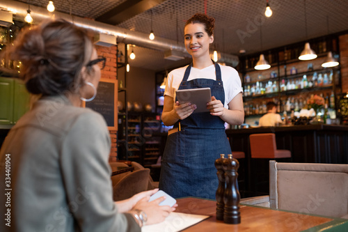 Happy young waitress with digital tablet standing in front of female guest