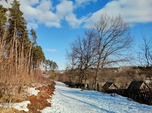 Spring Sunny Landscape With A Snow Covered Road Along The Forest On One Side And Trees Leaning Towards Old Houses On The Other Side Against A Blue Sky With Clouds
