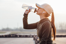 Beautiful Girl At Morning Workout Drinks Water From A Bottle