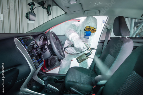 Obraz Clean surfaces in car with a disinfectant spray. Help kill coronavirus in  car after going out. - fototapety do salonu