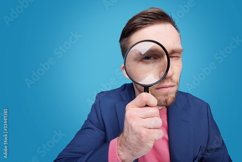 Photo Serious young male detective holding magnifying glass by right eye