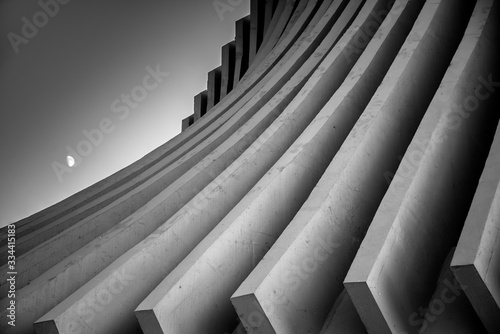 Black and white image of concrete roof beams sweeping down dramatically in curves with the moon rising in a dusk sky Canvas-taulu