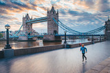 Fototapeta Londyn - Alone runner in empty streets of london in Coronavirus, Covid-19 quarantine time. Tower Bridge in background