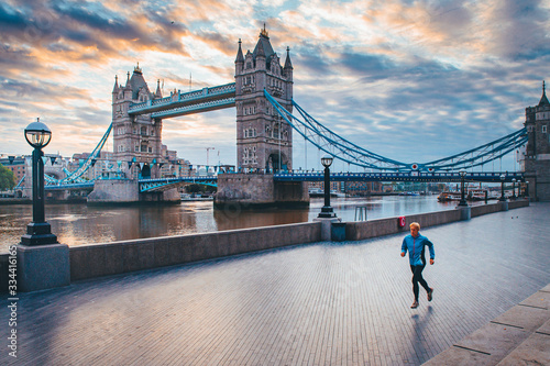 Fototapeta Alone runner in empty streets of london in Coronavirus, Covid-19 quarantine time. Tower Bridge in background obraz