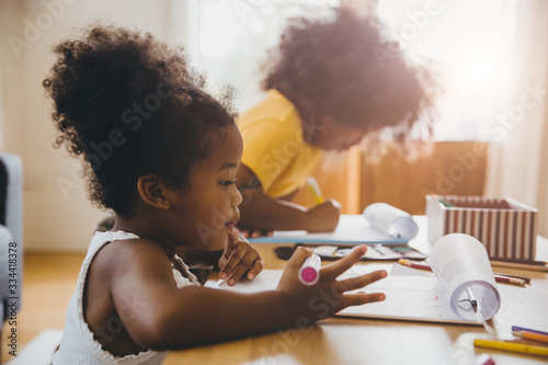 American Black preschool daughter kids doing homework learning education with her sister living together at home.