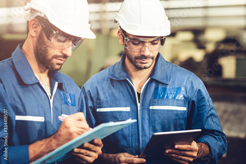 Engineer audit worker working team together with safety uniform and white helmet to work in industry factory handle tablet and checklist.