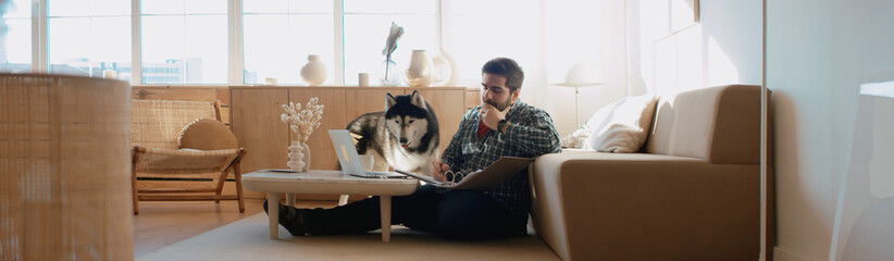 FototapetaMiddle Eastern male working from home, having a video call, dog sits near him. Stay home, quarantine remote work