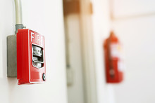 Manual Pull Fire Alarm Switch Safety System Box Installed And Fire Extinguisher On White Wall Background.