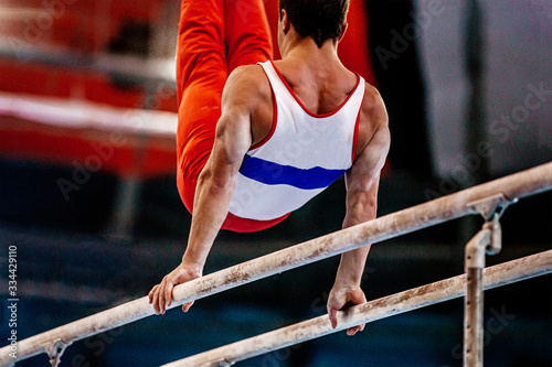 men gymnast perform exercise on parallel bars Canvas Print