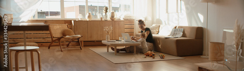 Obraz Caucasian mother working from home, having a work video call, daughter playing nearby. Stay home, quarantine remote work - fototapety do salonu