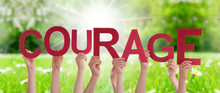 People Hands Holding Colorful French Word Courage Means Do Not Give Up. Sunny Green Grass Meadow As Background