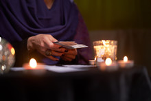 Close-up Of Soothsayer Guessing On Cards Sitting At Table With Burning Candles, Magic Ball