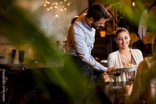 Fototapeta Smiling young female friends at a restaurant with waiter serving dinner obraz