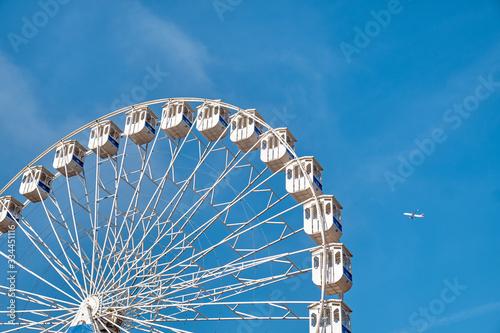 Fototapeta Ferris wheel and a plane. Lisbon, Portugal. obraz
