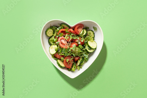 Fotografija Fresh salad with tomato, cucumber, vegetables, microgreen radishes in plate shape of heart on green