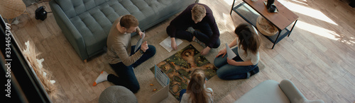Foto OVERHEAD Family - father, mother and two kids playing a board game together
