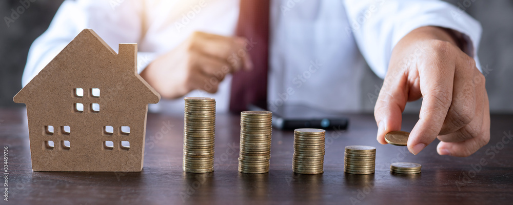 Fototapeta Save to real estate, property owner get money to home concept, small wooden house model on table with hand stacked coins to rent or buy above mentioned residence with cash to bank agency