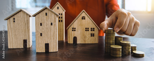 Fototapeta Save to real estate, property owner get money to home concept, small wooden house model on table with hand stacked coins to rent or buy above mentioned residence with cash to bank agency obraz