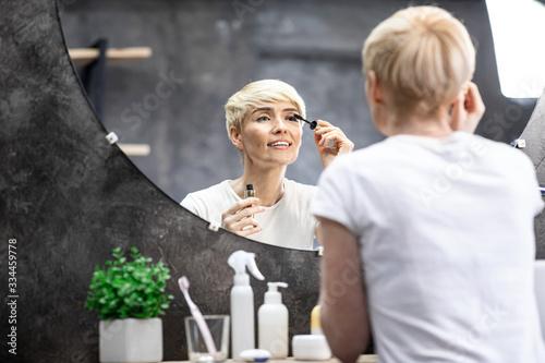 Mature lady applying mascara on eyelashes in bathroom at home Wallpaper Mural