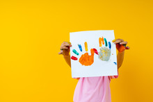 Young Kid Holding Paper Art On Yellow Background